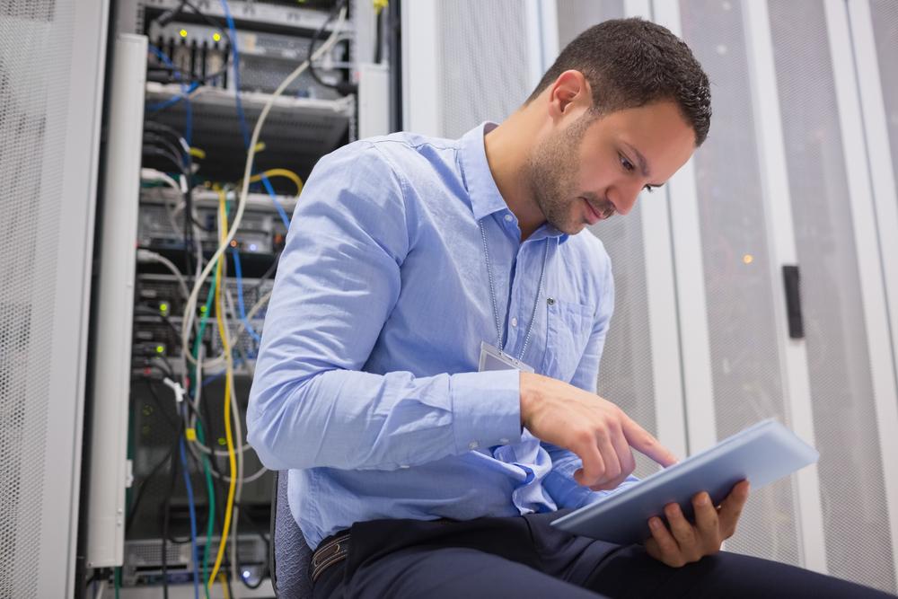 Man,Using,Tablet,Pc,Beside,Servers,In,Data,Center
